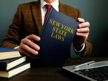 Lawyer shows New York State Law book.